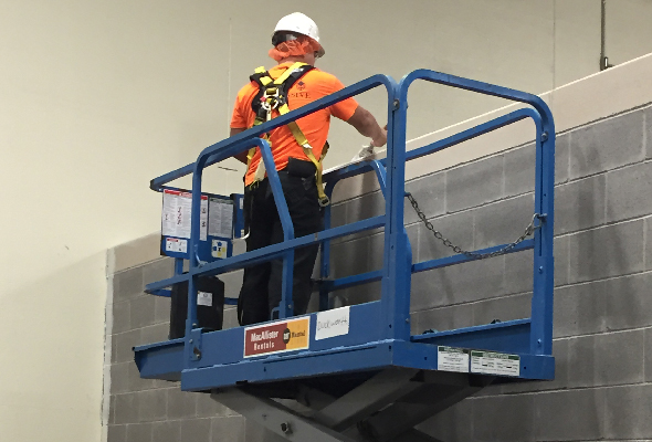 A man in safety orange uses a scissor lift. All part of industrial painting contractors normal routines.
